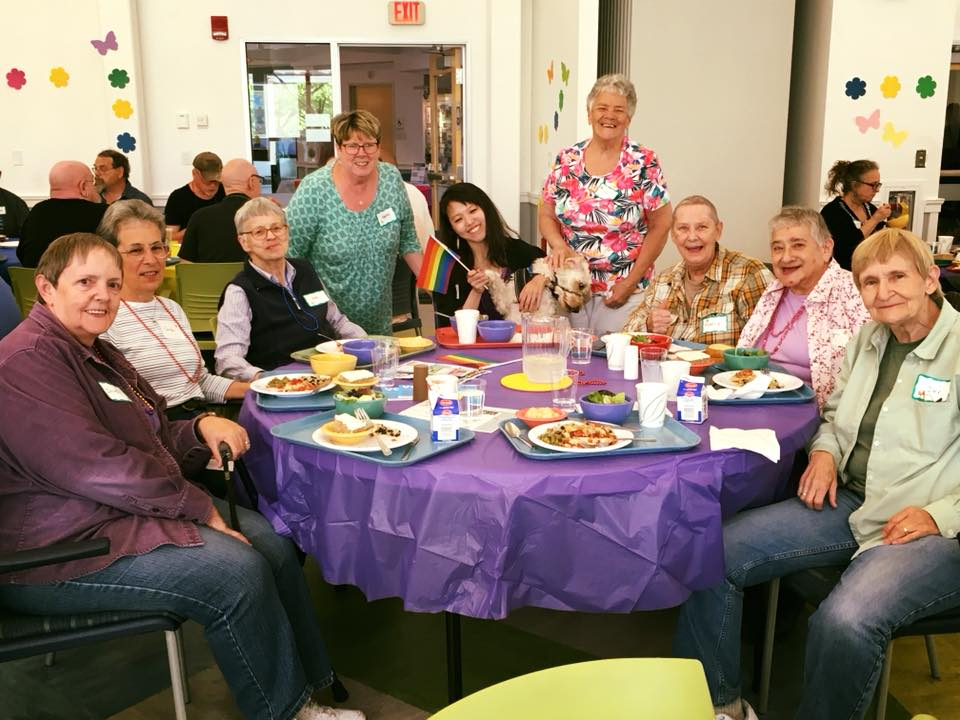 nine people smiling while sitting around a purple table with plates of food on it