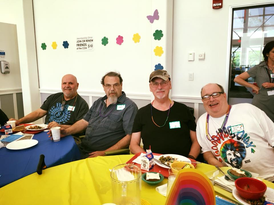 four people sitting around yellow table smiling
